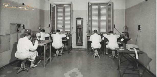 Laboratorio di orologeria foto storica anni 50 in bianco e nero di orologiai al lavoro _ ambiente di lavoro_ workplace during the 50s_watchmaking service centre in Rome